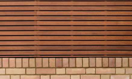 Stained Iroko Slatted Panels Fitted to Top face of a Wall